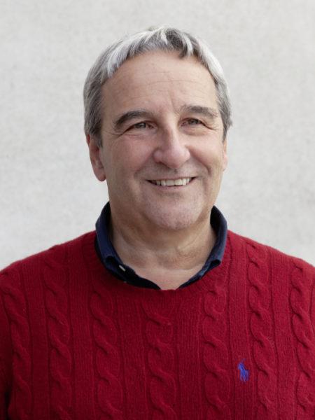 Ritratto a mezzo busto di Marco Mario Zafferoni, direttore generale dello Studio Tecnico Zafferoni. Il soggetto sorridente ha i capelli corti, lisci e brizzolati e gli occhi celesti. Indossa una polo blu scuro sotto un maglione rosso con il logo Ralph Lauren.